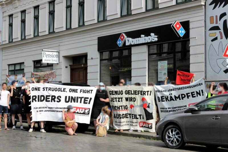 Demonstrant:innen mit Transparenten direkt vor einem Domino's-Store in Leipzig