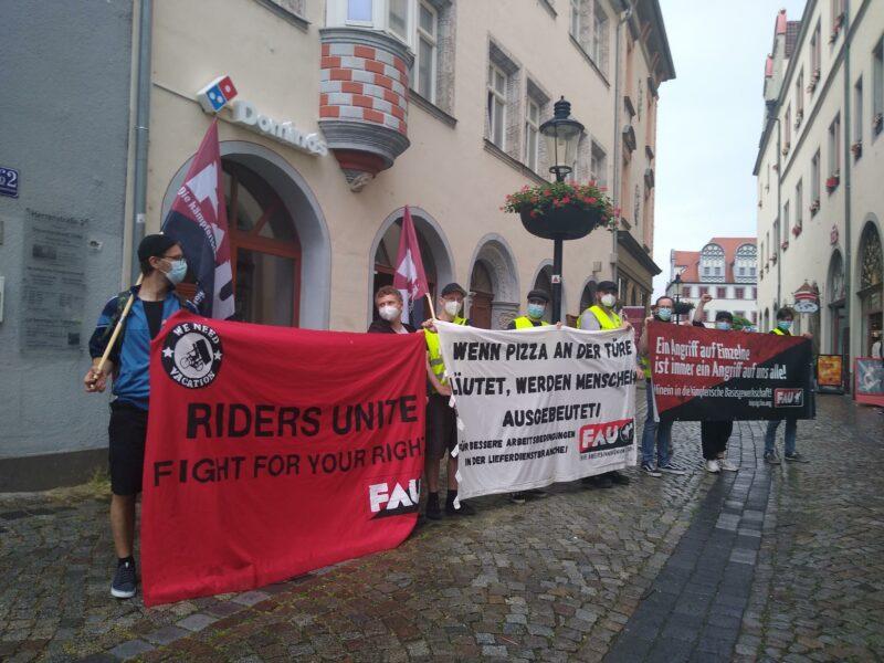 Mitglieder der FAU mit Transparenten vor der Domino's-Pizza Filiale in Naumburg