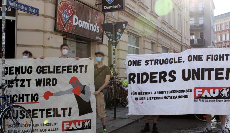 Demonstrant:innen mit Transparenten vor dem Domino's-Store in Plagwitz